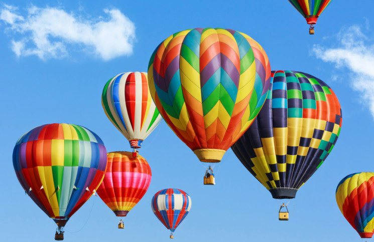 Image of six hot air balloons against a blue sky.
