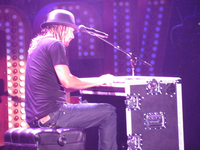 Image of musician Kid Rock play piano on a stage.